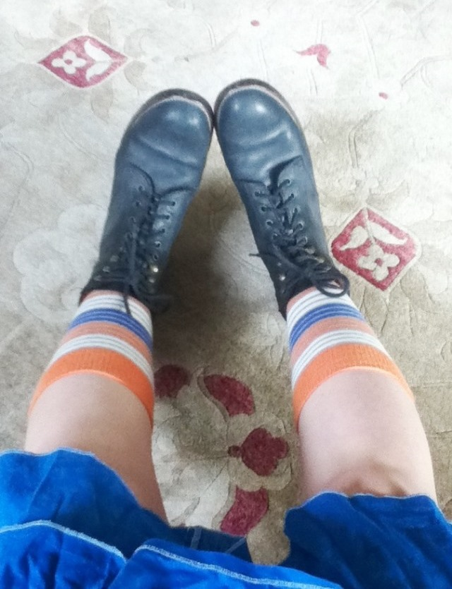black lace-up boots, orange and blue striped socks