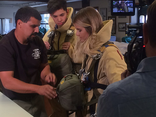 "Luis Gomez runs a safety check to see how well Disney Channel's ""Movie Surfers"" Golan Yosef and Taryn Brooks met the mark in their test to suit up in smokejumper gear within two minutes of getting the call to action. (U.S. Forest Service/Leo Kay)"