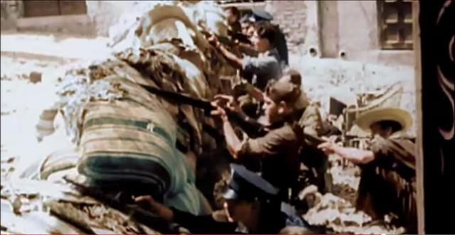 Barricada con milicianos disparando en la Cuesta de las Armas. Captura de un vídeo real a color de la Guerra Civil en Toledo en el verano de 1936