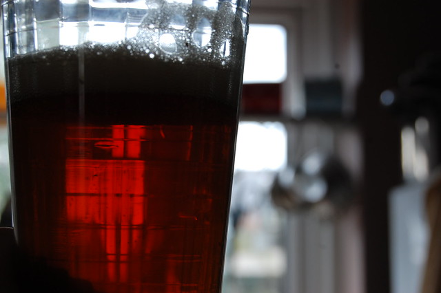 A glass of deep red-orange beer