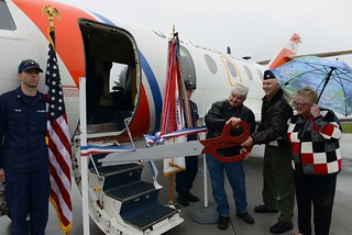 Willis Van Dusen,  Mayor of Astoria, Oregon, Capt. Bruce Jones, Coast Guard Sector Columbia River commander and Tita Montero, Tongue Point Job Corps Center business and community liaison, cut a ribbon in recognition of the newly completed HU-25 Falcon jet display project during a ceremony at Sector Columbia River in Warrenton, Oregon, May 9, 2014.Tongue Point Job Corps students and personnel worked closely with Coast Guard Sector Columbia River personnel to plan and complete the project.U.S. Coast Guard photo by Petty Officer 3rd Class Nate Littlejohn