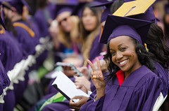 SF State student displaying a peace sign at graduation