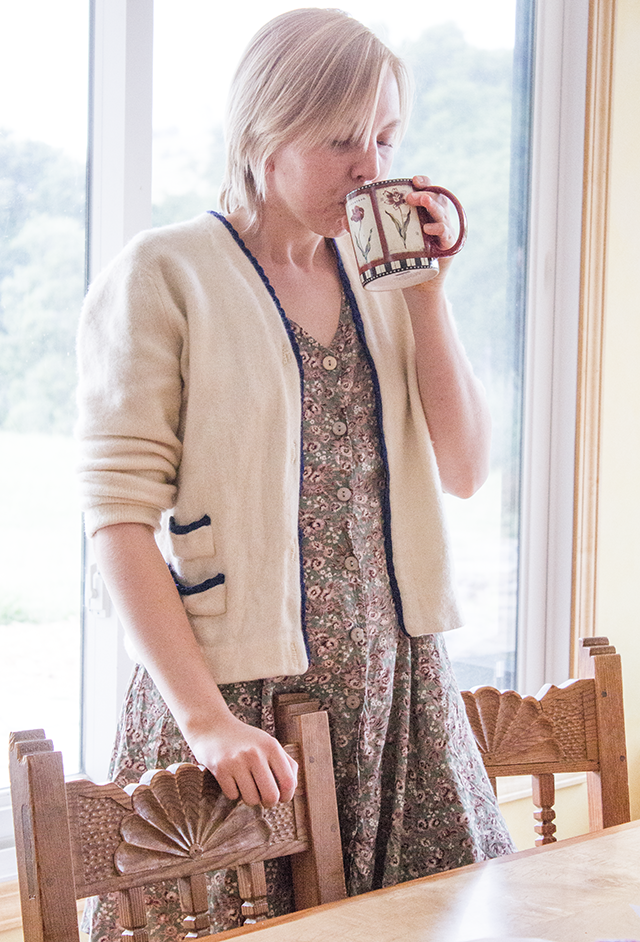 cream cashmere sweater with royal blue trim, floral green dress, drinking from a floral coffee mug