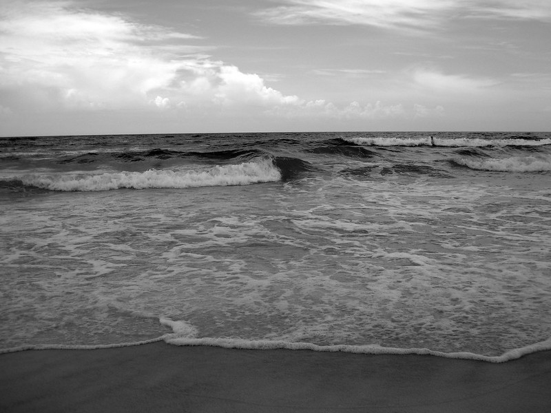 Black and white waves crashing on a beach