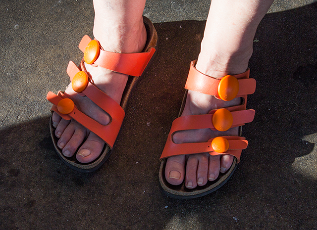 orange Birkenstock sandals with big round buttons