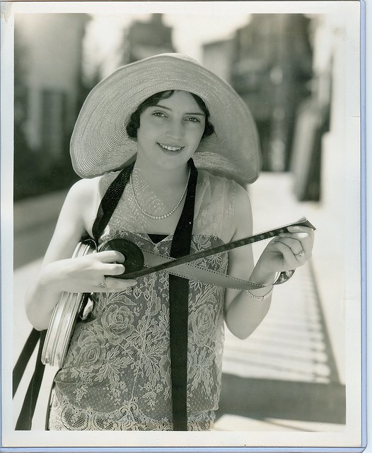 Gladys  Belmont with roll of film ...checking to see how she looks