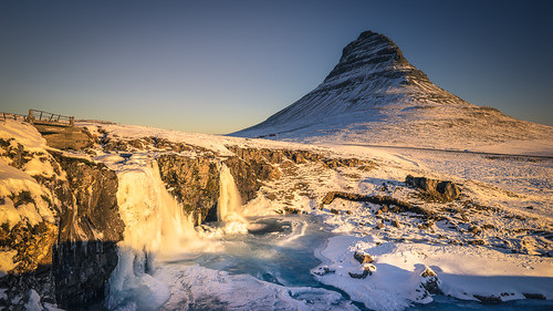 blue cold golden ice iceland kirkjufell kirkjufellfoss light mountain orange peak sky snow sunrise water waterfall winter