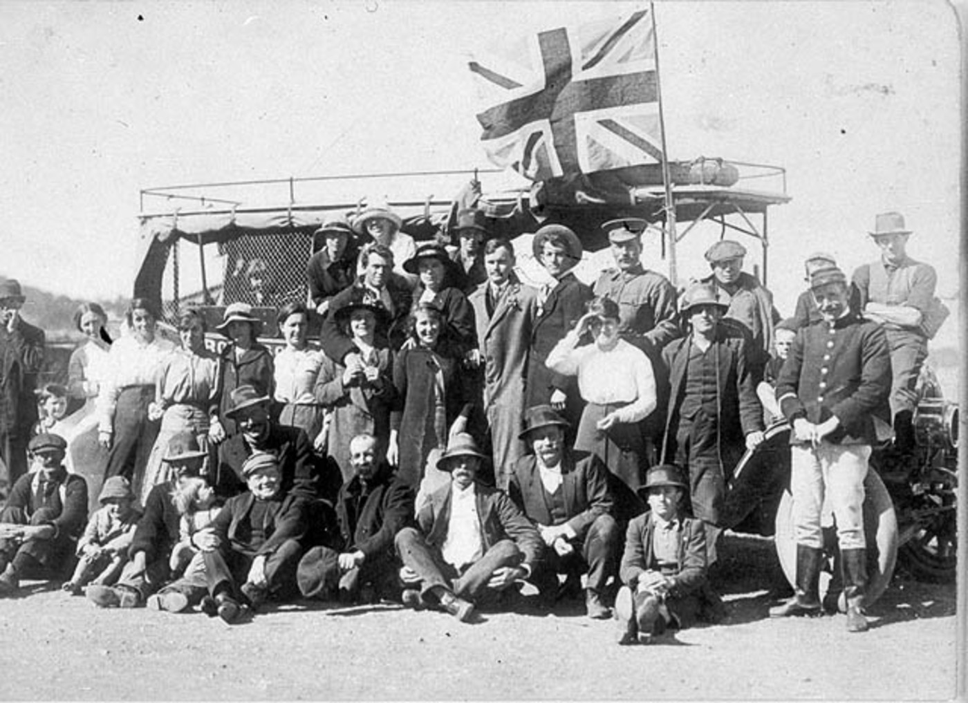 Enlisting for World War I. Recruiting Officer (beside flag ) with volunteers and their relatives and friends. Babe Cooper (second from the left of recruiting officer.) Bert Cooper has his arm around his sister. Constable McGrath is in uniform - Jerseyvill