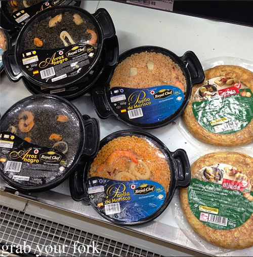 Ready-to-heat paella and tortilla espanola in a Spanish supermarket