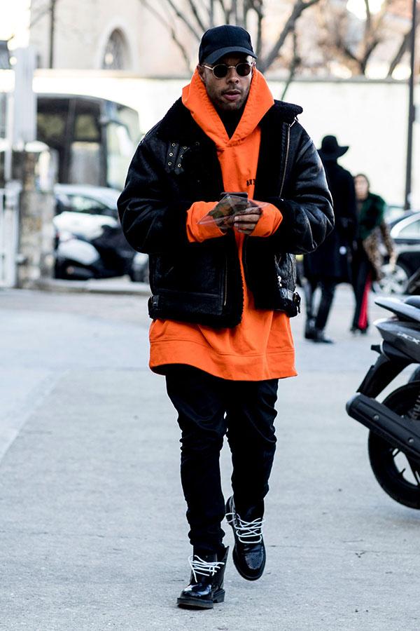 黒キャップ×黒B-3フライトジャケット×オレンジパーカー×黒パンツ×黒ブーツ