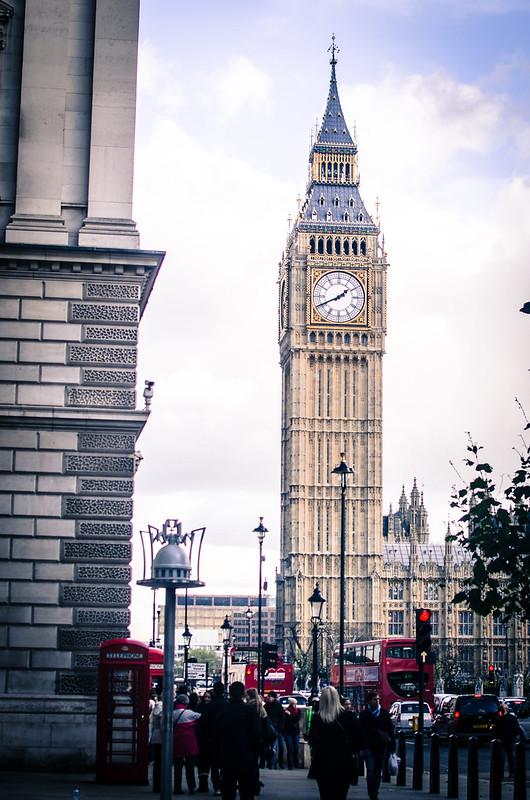 Double Decker red buses circle around London's landmark Big Ben.