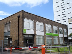 "A squarely-built brick building with large windows divided into long rectangular panes.  A sign reads ""jobcentreplus"" in white and yellow letters on a bright green background."