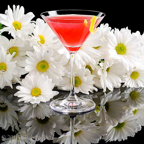 Rum Daisy Cocktail in cocktail glass, with daisies in background