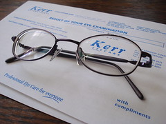 "A pair of oval-framed glasses sitting on top of two pieces of paper on a wooden table.  The top piece of paper is a compliments slip and the bottom piece is headed ""Result of your eye examination""."