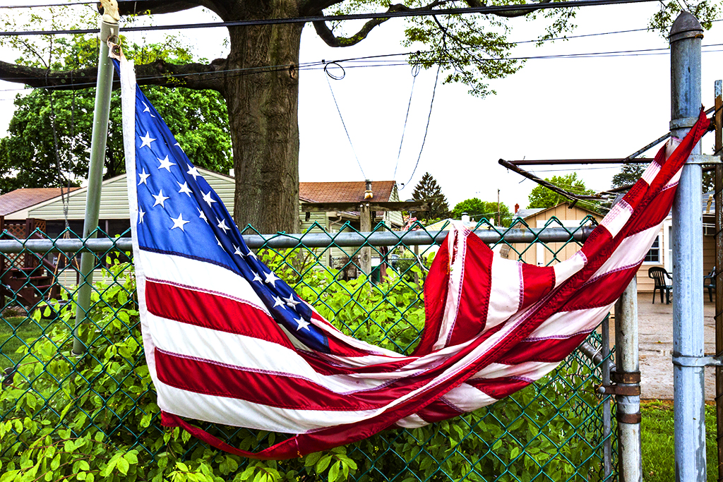 Torn-flag-stuck-on-fence--Levittown