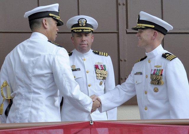 PEARL HARBOR -  Capt. John M. Figuerres, left, former commanding officer of Afloat Training Group Middle Pacific, shakes hands with Cmdr. Timothy Wilke, commanding officer of Afloat Training Group Middle Pacific, during a change of command ceremony at Ford Island, Joint Base Pearl Harbor-Hickam.
