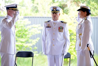 Former Coast Guard Marine Safety Unit Savannah, Ga., commanding officer Joseph Loring and new commanding officer Cmdr. Amy Beach salute each other to signify transfer of command of the MSU as Coast Guard Sector Charleston, S.C. Commander Capt. Ric Rodriguez watches Thursday, June 12, 2014. A change of command ceremony is a time-honored military tradition which formally recognizes total transfer of responsibility and authority of a unit from one individual to the other. (U.S. Coast Guard photo by Petty Officer 1st Class Lauren Jorgensen)