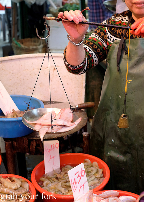 Weighing seafood using an old-fashioned balance scale with weights at the Gage Street market in the Central district, Hong Kong