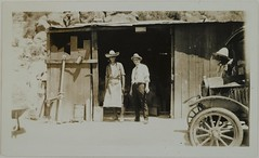 Two men in a doorway and another man by a car, all wearing hats, probably in Chihuahua, Mexico, 1925.