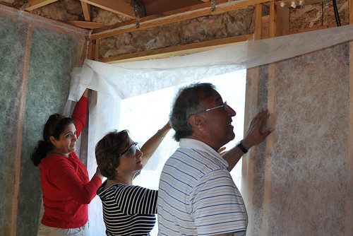 Teresa Hernandez, Administrator Tony Hernandez, and US Representative Suzanne Bonamici prep the walls for insulation.