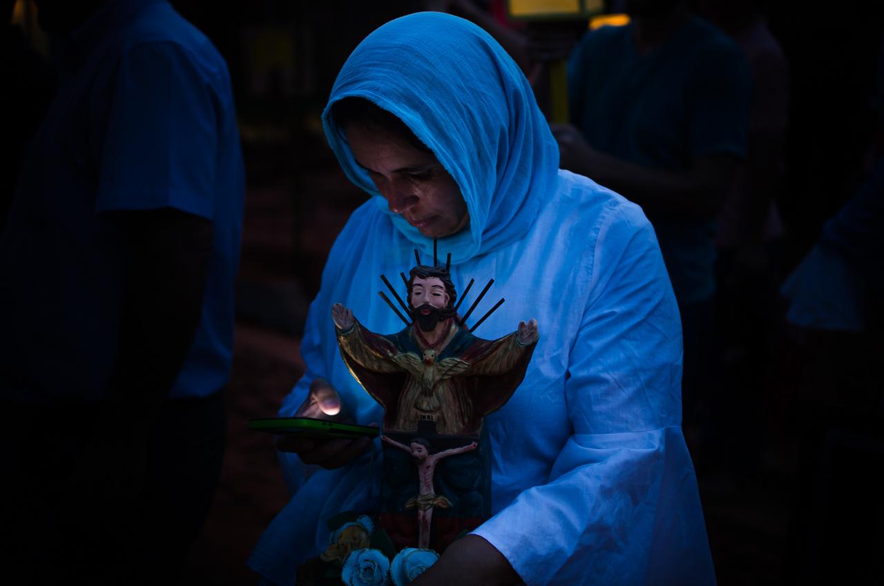 Una señora integrante del elenco religioso de la procesión de Tañarandy, revisa sus mensajes mientras todos esperan la hora indicada para el comienzo del recorrido por los 3 kilómetros que comprenden la ruta de peregrinación. (Elton Núñez).