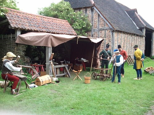 Various historical re-enactors in medieval garb, and one Napoleonic soldier, at work around an awning.