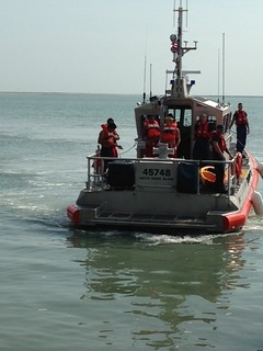 A Coast Guard Station South Padre Island boatcrew brings two rescued kayakers back to the station after their kayak capsised dangerously close to the jetties Wednesday, July 23, 2014. The male kayakers were 16 and 18 years old. U.S. Coast Guard photo by Station South Padre Island.