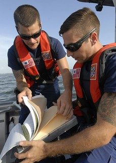 Petty Officer 2nd Class Justin Peed, a boarding officer at Coast Guard Station Sand Key, Fla., assists Petty Officer 3rd Class Brian Olsen with paperwork during a vessel boarding near Sand Key Saturday, June 28, 2014. The boarding conducted is a safety check to make sure a boater has the proper safety equipment on their vessel. (U.S. Coast Guard photo by Petty Officer 1st Class Crystalynn A Kneen)