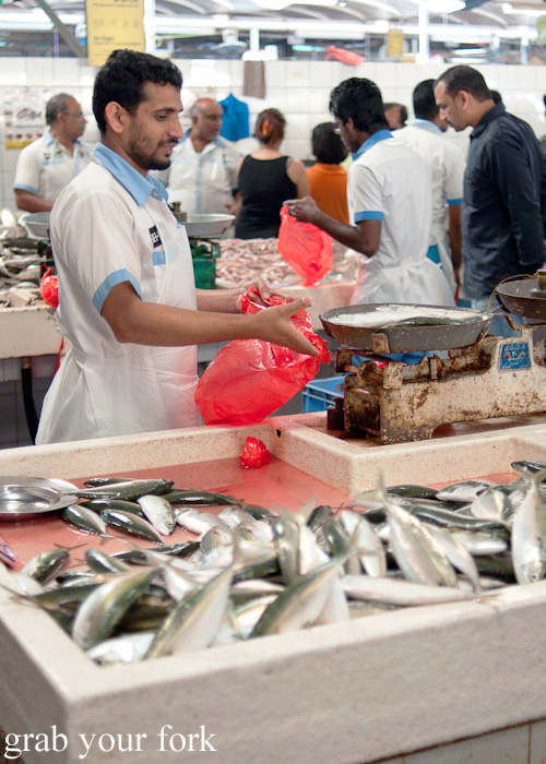 Weighing fish on scales at Dubai Fish Market in Deira