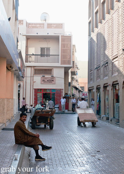 Delivery carts and locals in Meena Bazaar, Dubai