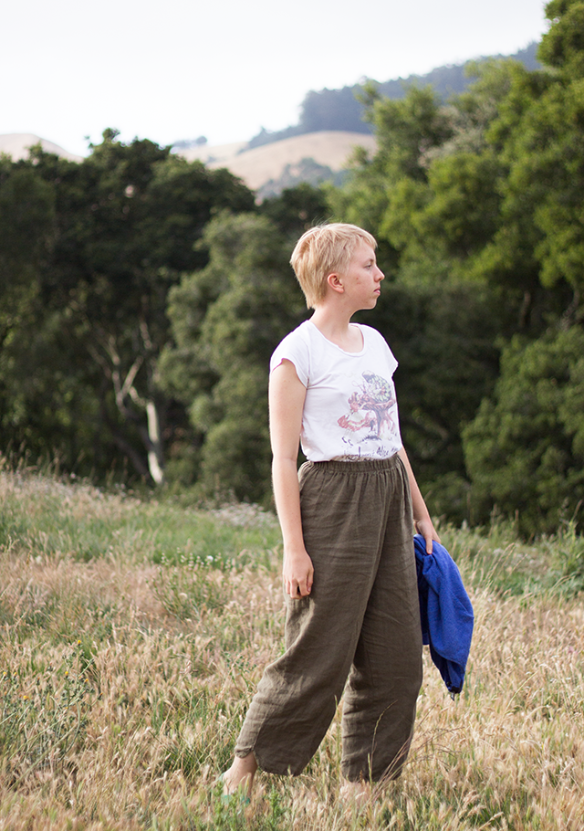 white Alice in Wonderland t-shirt, brown linen trousers, forest setting