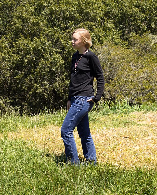 black long-sleeve shirt, bootcut blue jeans, warm sunshine, green grass