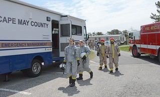 Members of the Cape May County Chemical, Biological, Radiological, and Nuclear Emergency Task Force (in silver) and Coast Guard firefighters (in brown) from Training Center Cape May, N.J., participate in a full-scale antiterrorism/force protection at the training center April 28, 2014. Numerous law enforcement, EMS and military personnel are participating in the two-day exercise aimed at improving the community's response to a terrorist attack. (Coast Guard photo by Chief Warrant Officer Donnie Brzuska)