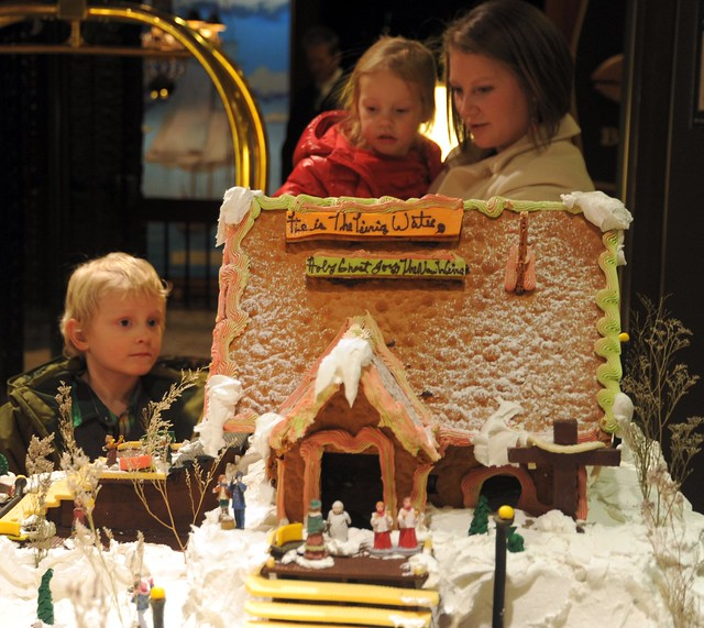 Enjoying the snowy Gingerbread House of the Gingerbread Town, two children with their mom, hotel, Anchorage, Alaska, USA