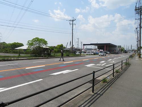 佐賀競馬場前の道路を横断する男性
