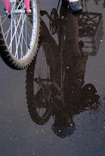 bike tire with bike and girl's reflection in puddle