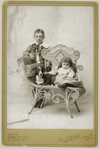 Two children, a dog and a wicker chair