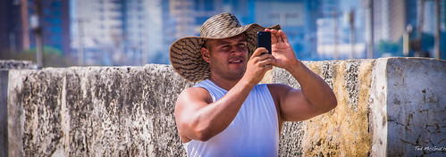 camera portrait male face muscles hat hands nikon colombia photographer arms teeth cellphone shooting cartagena retainingwall aiming brim d600 cartagenacolombia simplysuperb tedsphotos nikonfx