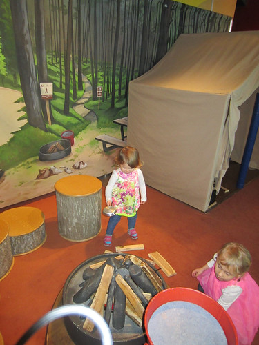 Olivia and Lily Anderson enjoy making camp at Betty Brinn Children's Museum. Lily (right) builds the fire as Olivia (left) preps the dinner. (Photo courtesy Leah Anderson)