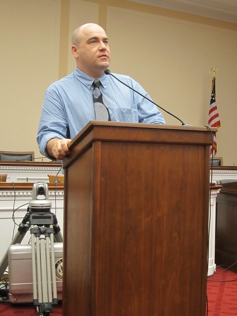 Photo of a man in a blue shirt and gray tie standing at a podium