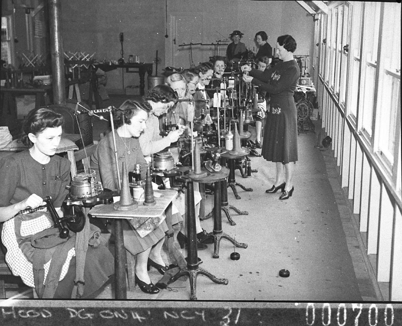 Women volunteers operating knitting machines (taken for Australian Comforts Fund), by Sam Hood March 1944