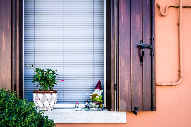 A family of reading gnomes enjoy their private Burano windowsill.