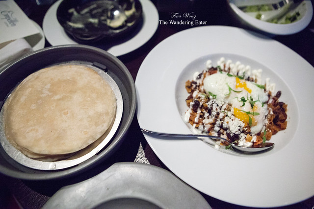 Chilaquiles Rojo, slow poached egg with black beans served with fresh tortillas
