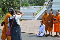 Some monk- tourists get a group photo taken with their family members
