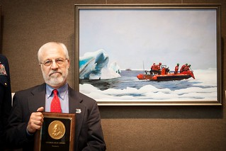 """The 2014 George Gray Award for Artistic Excellence recipient, Robert Selby, stands next to his painting, """"Chukchi reach"""" after receiving his award at the opening reception of the 2014 Coast Guard Art Program collection on view at the Salmagundi Club in New York City, June 26, 2014. The George Gray Award is named after COGAP's co-founder and champion, George Gray. (U.S. Coast Guard Photo by Petty Officer 2nd Class LaNola K. Stone)"""