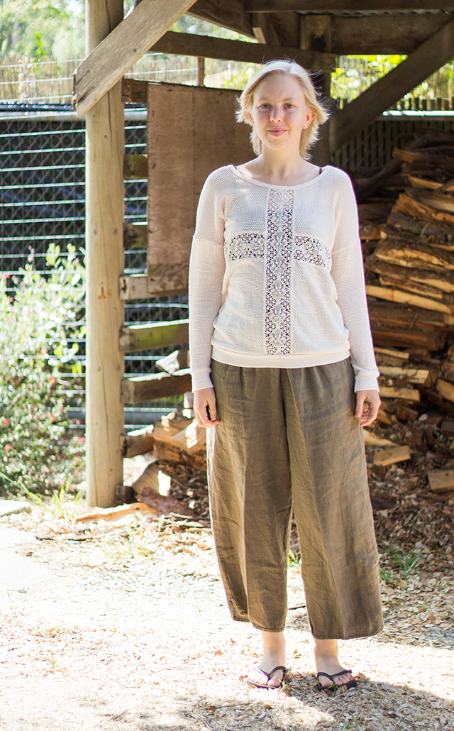 see-through cream lace sweater with cross details, loose brown linen trousers