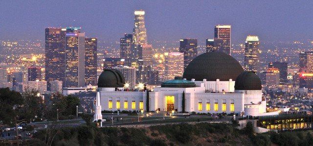 Griffith Observatory at night with downtown Los Angeles in the background.