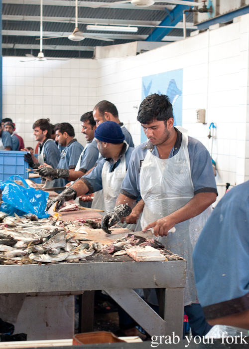 Fishmongers cleaning and gutting fish at Dubai Fish Market in Deira