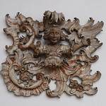A wood carving with an angelic youth ensconced in a burst of Rococo ornament.