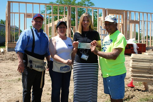 USDA Ohio Rural Development State Director Tony Logan (left) joins Rural Development Loan Underwriter Karen Westrick, homeowner Michelle Amrine and Habitat for Humanity Union County Board President Jim Cesa for a check presentation at the Marysville work site. As part of USDA's ongoing Homeownership Month observance, Rural Development employees spent the day helping frame exterior walls of Amrine's house. (USDA Photo by Heather Hartley)